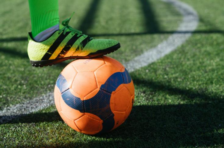 imagem ampliada do pé de um jogador com chuteira verde em cima de uma bola laranja e azul