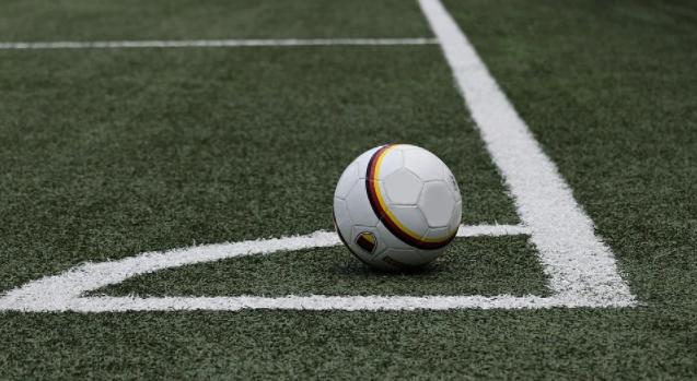 bola de futebol branca com uma listra preta e laranja no canto de um campo de futebol