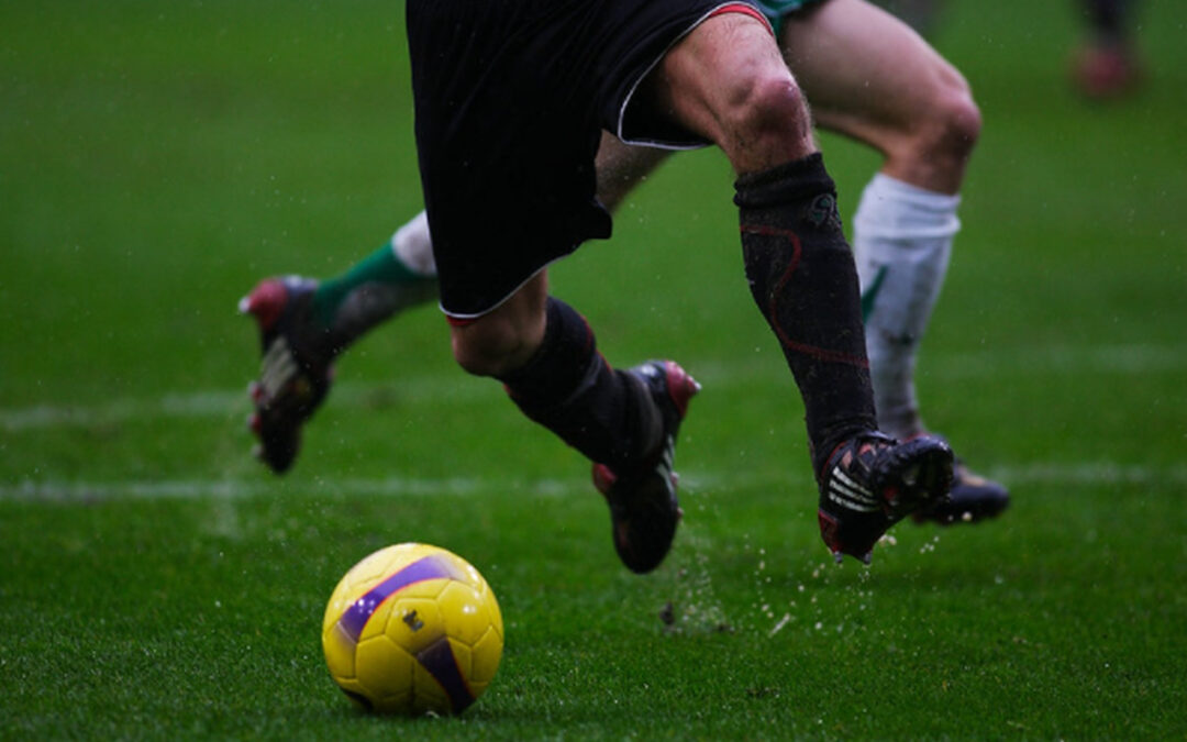 dois jogadores de futebol em campo jogando o esporte