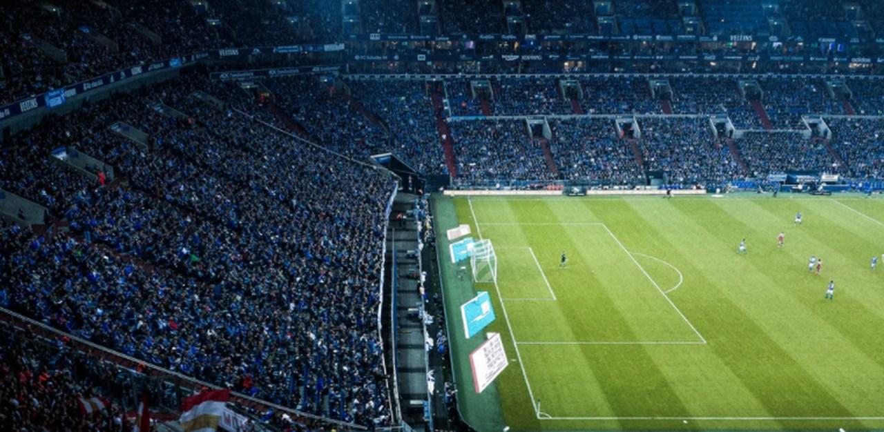 estádio de futebol com arquibancadas lotadas e sem jogadores em campo