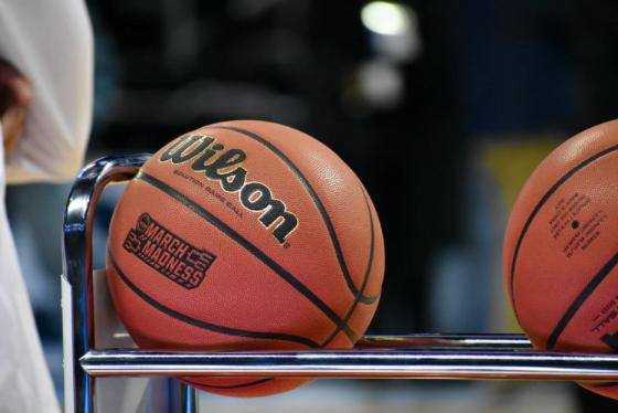 pessoa aproximada de uma estrutura de ferro que guarda as bolas de basquete que serão usadas durante o jogo