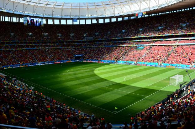 estádio de futebol com campo vazio e arquibancadas lotadas