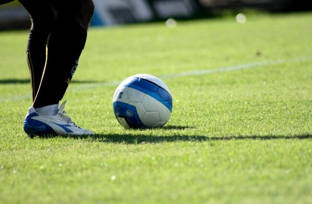 imagem dos pés de jogador com chuteira branca e azul perto de uma bola de futebol