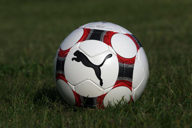 bola de futebol com detalhes vermelhos, verdes, banco e preto parada em campo de futebol