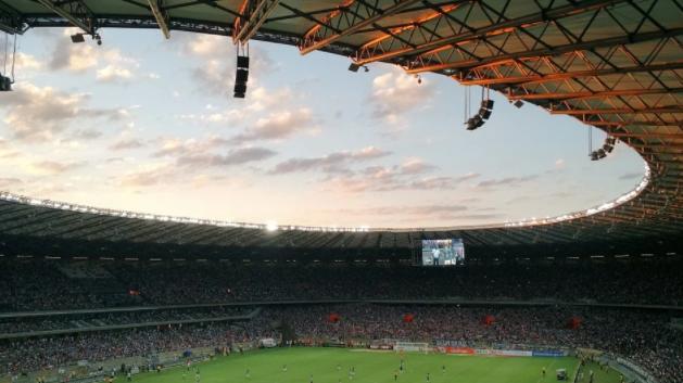 estádio de futebol com teto redondo, atletas em campo e arquibancadas cheias