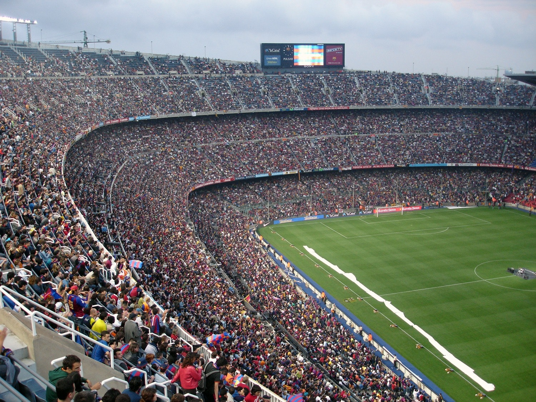 Estádio de futebol em dia de torneio lotado de torcedores.