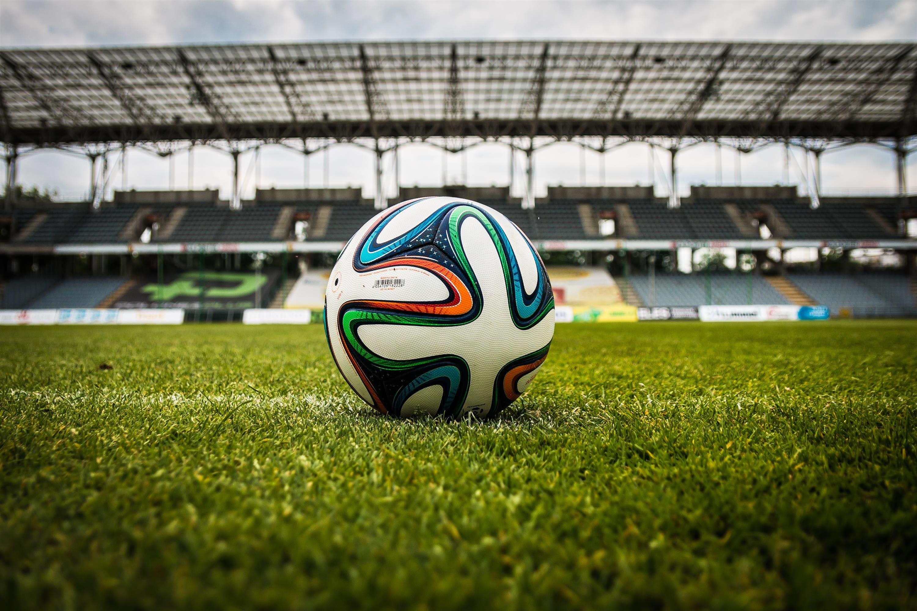 Bola de futebol multicolorida em campo de futebol.
