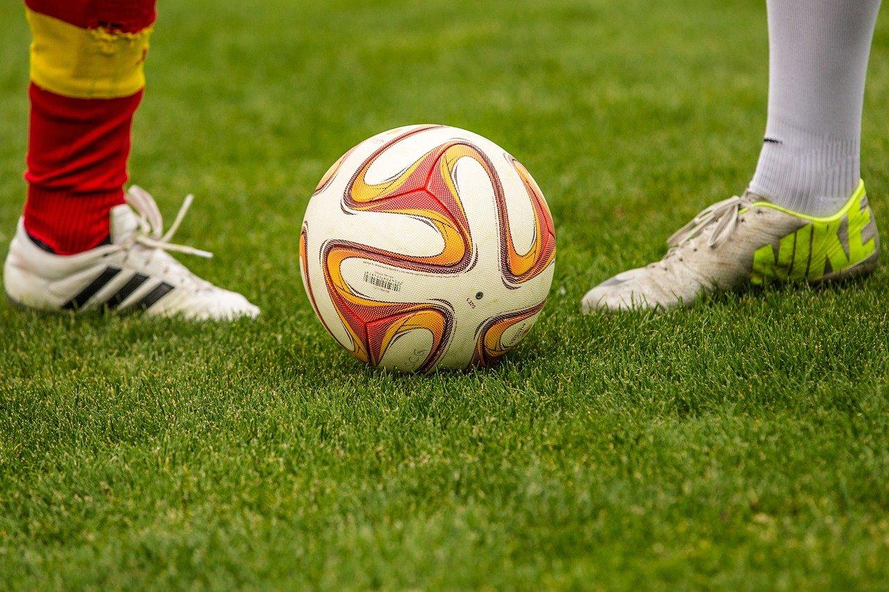 imagem ampliada dos pés de dois jogadores perto de uma bola de futebol