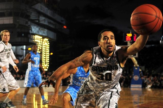 jogadores de basquete no meio de partida com um jogador tentando pegar a bola que está quase escapando de sua mão