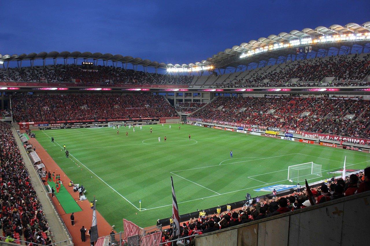 vista aberta de campo de futebol com jogadores em campo