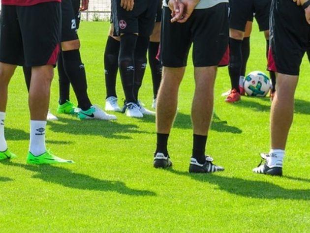 Jogadores em círculo no campo de futebol.